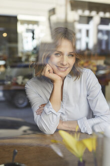 Portrait of smiling woman in a coffee shop looking out of window - PNEF00799