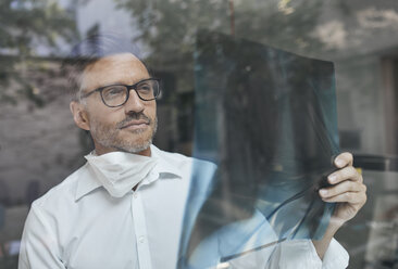 Portrait of radiologist behind windowpane looking at x-ray image - PNEF00820