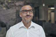Portrait of smiling man with stubble behind windowpane wearing white shirt and glasses - PNEF00823