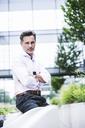 Portrait of confident businessman outside office building - UUF14665