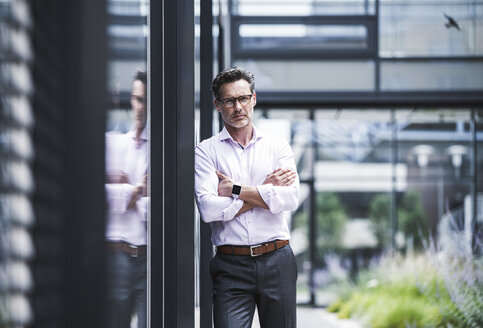 Portrait of serious businessman outside office building - UUF14671