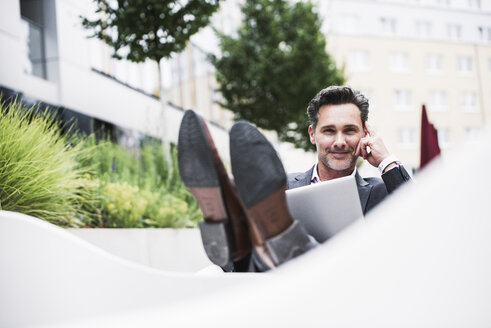 Portait of relaxed businessman with laptop outside office building - UUF14692
