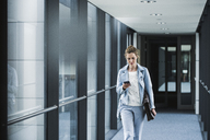 Businesswoman with cell phone walking in office passageway - UUF14698