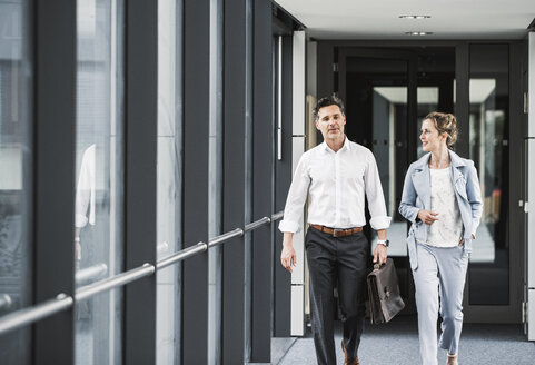 Businesswoman and businessman walking in office passageway - UUF14701