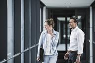 Businesswoman and businessman arguing in office passageway - UUF14707