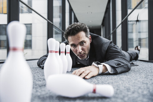 Diligent manager lying on the floor in office passageway with pins - UUF14713