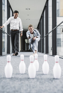 Happy businessman and businessman bowling in office passageway - UUF14716