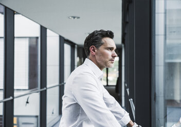 Businessman looking out of window in office passageway - UUF14722