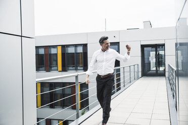 Cheering businessman walking on skywalk at office building - UUF14728