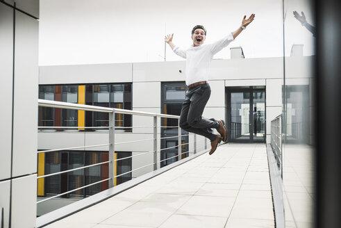 Cheering businessman jumping on skywalk at office building - UUF14731