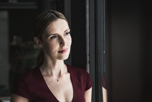 Portrait of woman looking out of window - UUF14746