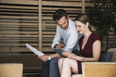 Businesswoman and businessman with tablet discussing in office lounge - UUF14758