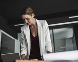 Businesswoman in office with laptop and plan on desk - UUF14764