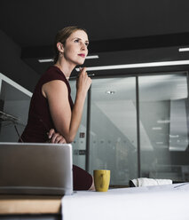 Businesswoman in office with plan and laptop on desk thinking - UUF14770