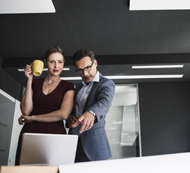 Businesswoman and businessman in office discussing with laptop and plan on desk - UUF14773