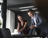 Smiling businesswoman and businessman in office discussing plan on desk - UUF14776