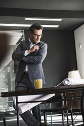 Businessman in office looking at plan on desk - UUF14782