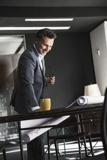 Smiling businessman in office looking at plan on desk - UUF14785