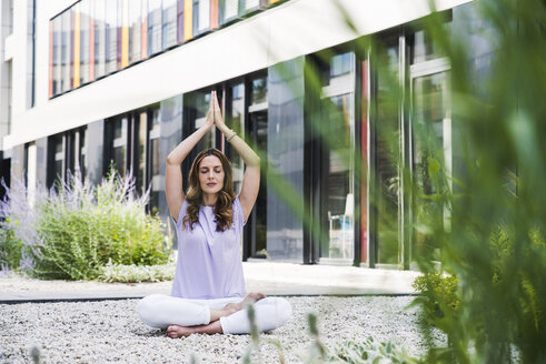 Woman practicing yoga in garden outsde office building - UUF14788