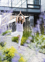 Woman practicing yoga in garden outsde office building - UUF14791