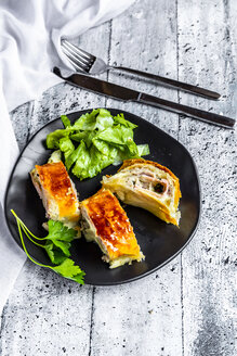 Swiss roll, puff pastry with sausage meat, cheese, onion, parsley and salad on plate - SARF03867
