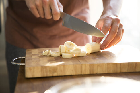 Man's hand chopping banana with kitchen knife - MFRF01152