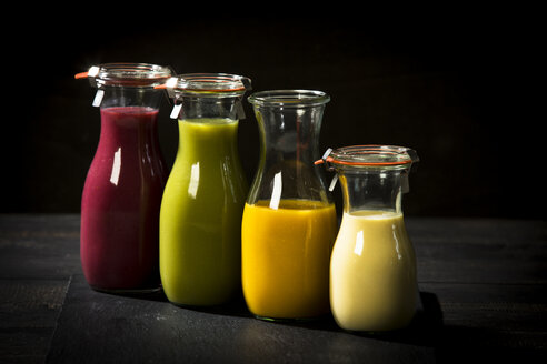 Four glass bottles of different smoothies - MAEF12680