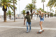 Spain, Barcelona, young man teaching his girlfriend skateboarding - WPEF00720