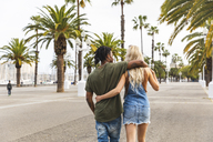 Spain, Barcelona, back view of multicultural young couple walking arm in arm on promenade - WPEF00723