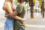 Spain, Barcelona, multicultural young couple embracing on promenade, partial view - WPEF00726