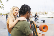 Multicultural young couple with longboard relaxing at harbour - WPEF00729