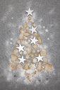 Christmas cookies and white stars forming Christmas Ttee on grey background - GWF05618