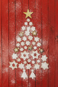 Christmas cookies and star-shaped Christmas baubles forming Christmas tree on red wooden background - GWF05621