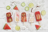 Homemade watermelon and coconut cream ice lollies with lime and cucumber slices, fresh coconut chips on ice cubes - GWF05624