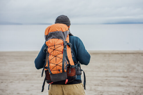 Man with backpack looking at lake, rear view - VPIF00411