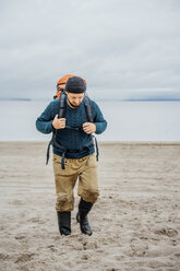 Man with backpack, walking on the beach - VPIF00414