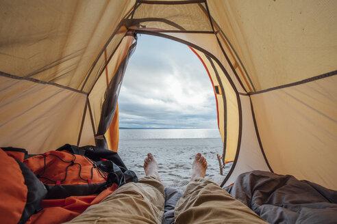 Feet of man, lying in tent on beach - VPIF00417