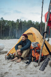 Backpacker sitting in front of his tent on the beach - VPIF00420