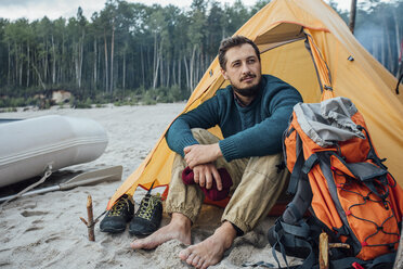 Backpacker sitting in front of his tent on the beach - VPIF00423