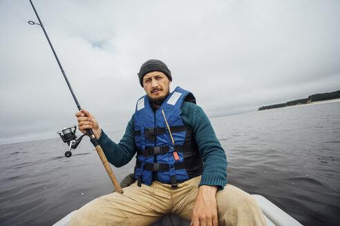 Man sitting on boat fishing with fishing rod - VPIF00429