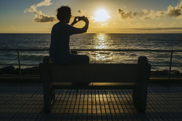 Spain, Canary Islands, Gran Canaria, Man taking a photo with mobile phone at sunset - KIJF01976