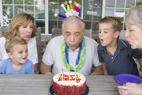 Senior man blowing out candles on birthday cake with family - ISF19383