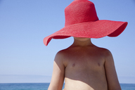 Young boy hidden by large red sunhat - ISF19536