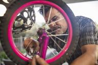 Man fixing wheel of children's bicycle - ZEF15908