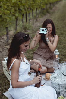 Friends having picnic in a vineyard, one woman taking pictures with instant camera - MAUF01624
