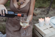 Woman pouring wine in glass on a picnic in nature - MAUF01633