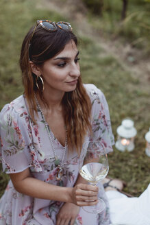 Woman at a summer picnic, drinking wine - MAUF01636