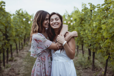 Twin sisters embracing at summer picnic in a vineyard - MAUF01642