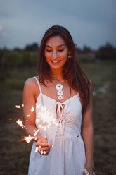 Young woman in nature, burning sparkler in the evening - MAUF01657