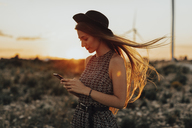 Portrait of young woman looking at cell phone by sunset - OCAF00338